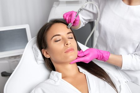 Beautiful woman with long hair, with clean fresh skin.Cosmetologist makes  procedure microdermabrasion on the face. Women's cosmetology in the beauty salon.