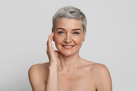Anti-Age Treatment. Portrait Of Attractive Nude Mature Woman With Beautiful Skin Posing At Camera Over Light Background, Copy Space